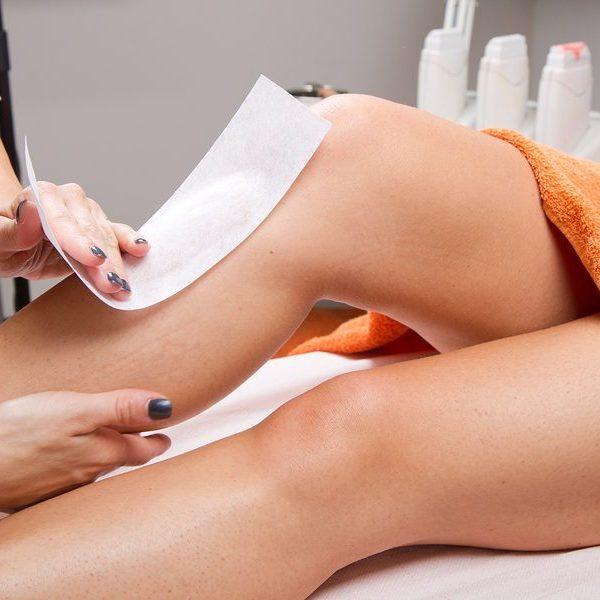 Beautician Waxing A Woman's Leg